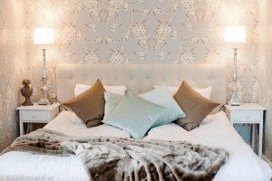 Blommiga tapeter, vita lampor och brunt överkast