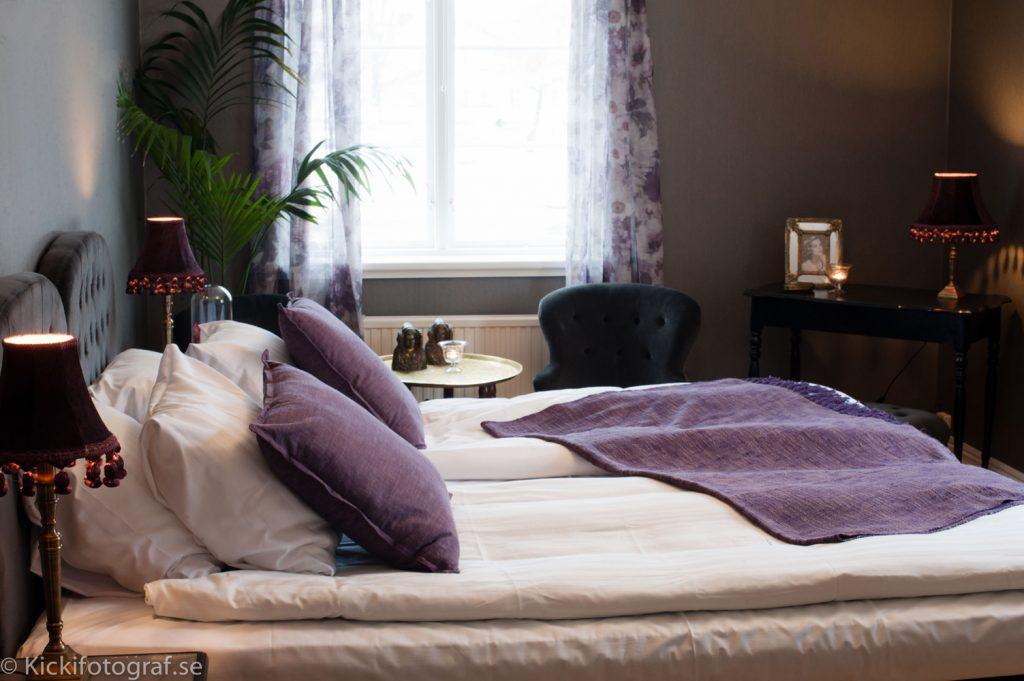 Sovrum med lila kuddar och överkast och lampor med toffsar