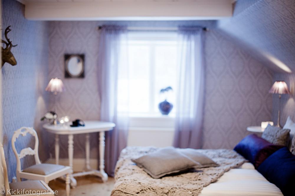 Lila sovrum med vita stolar och virkat överkast