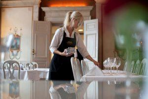 Servispersonal som dukar med servetter och glas