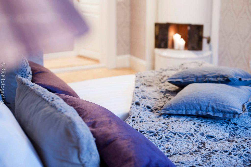 Kakelugn i bakgrunden samt lila täcke och kuddar på sängen