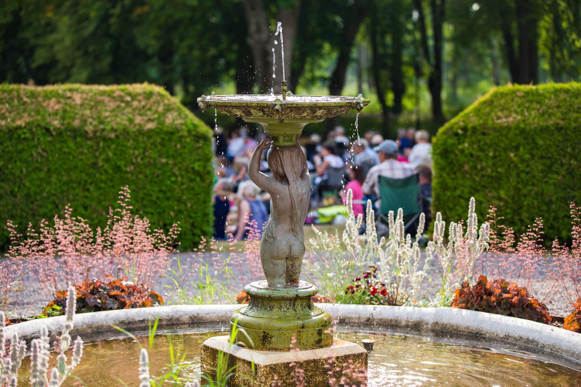 Slottstatyn med sprutande vatten och gröna buskar
