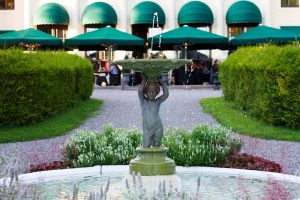 Slottsfontän med droppande vatten och gäster på terrassen i bakgrunden