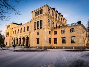 Slottet med snö utanför sam granar på terrassen