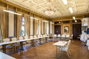 Konferenslokal Reuterskiöld på Slottet med vitt stukaturtak och kristallkrona