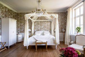 Sviten med sängen, fåtölj samt bord med blommor