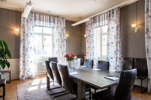 Konferenslokal Eleonora på Slottet med läderstolar och grått bord, blåa gardiner