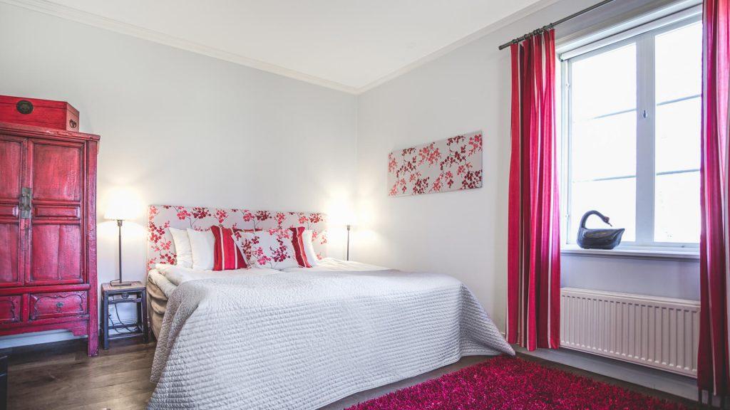 Hotellrum 28 i Vallonhuset, röd matta och röda gardiner