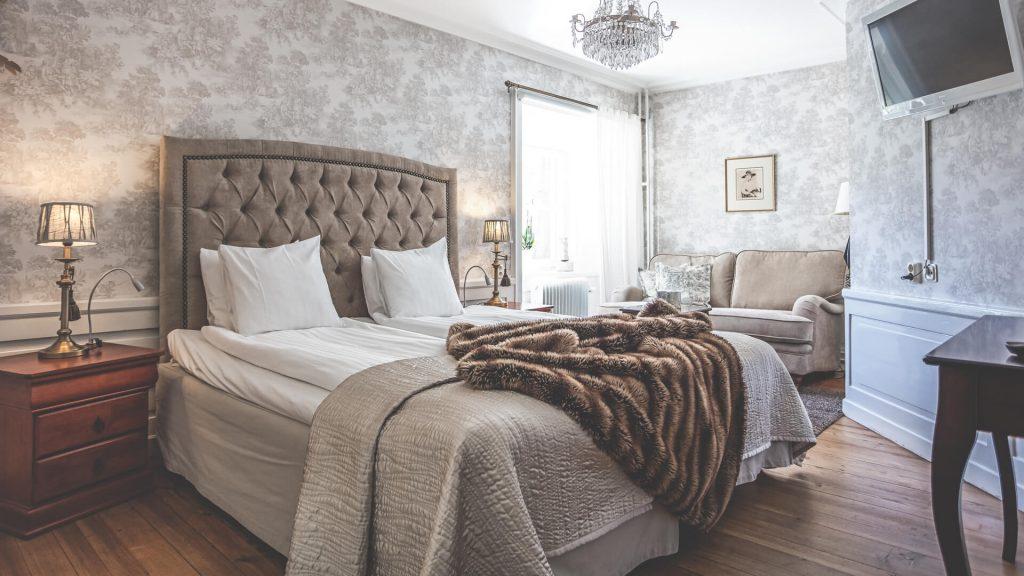 Dubbelrum med gråa tapeter, beige sängavel och kristallkrona