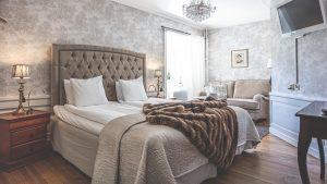 Hotellrum 9 på Slottet, brun sängavel och pläd på sängen