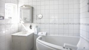 Badrum i Vallonhuset med vita klinkers och bubbelbad