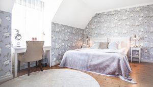 Hotellrum 40 i Vallonhuset med lila överkast och blommiga tapeter