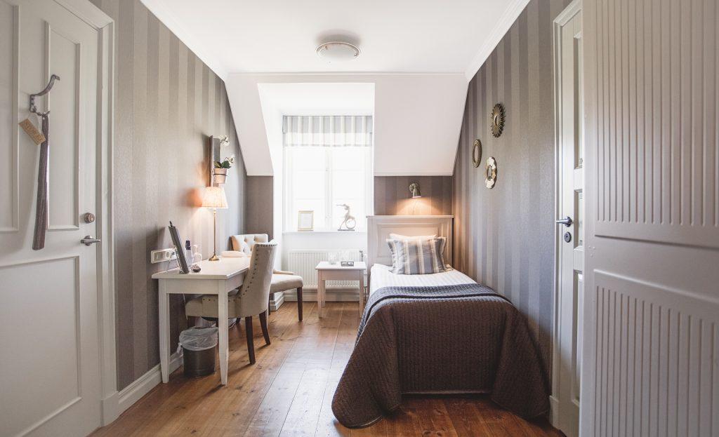 Enkelrum i Vallonhuset med brunrandiga tapteter samt säng med brunt överkast