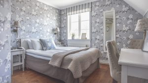 Queenbädd rum i Vallonhuset med blommiga gråa tapeter och säng med beige överkast