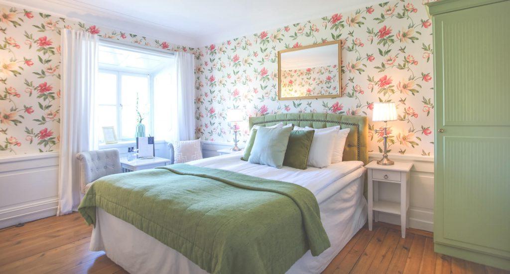 Dubbelrum med rosablommiga tapeter och säng med grönt överkast och kuddar