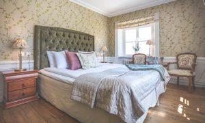 Dubbelrum med grön sänggavel med blommiga tapeter