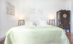 Hotellrum 29 i Vallonhuset, säng med grönt överkast