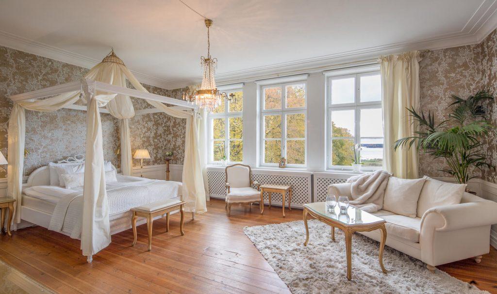 Hotellrum Sviten i slottet ena torn, sänghimmel, vit soffa och matta