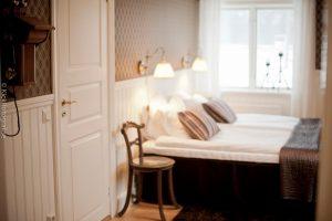 Rum med bruna tapeter och brunrandiga kuddar och överkast