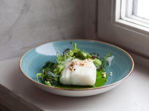 Uppläggning mat torsk och broccoli, blått fat ståendes i fönster