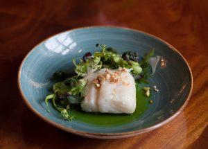Uppläggning mat torsk och broccoli, blått fat på brunt bord