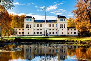 Höstbild med slottet, dammen och höstgula träd