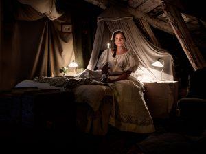 Slottspigan sittandes i säng på vinden