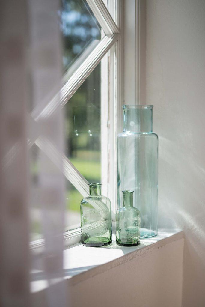 Detaljbild med gröna glasflaskor i fönster