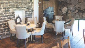 Ölstugan cafédel i Stenkvarn, fåtöljer med bord, trägolv och stenväggar