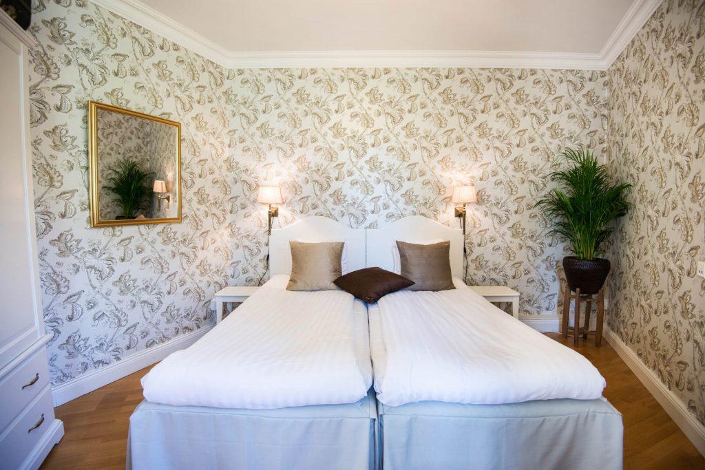 Grön växt och spegel i sovrum med beigeblommiga tapeter