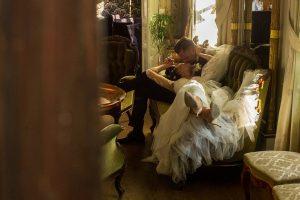 Brudpar kysser varandra sittandes i en soffa i salongerna