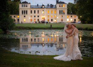 Brudpar står vid dammen med slottet i bakgrunden