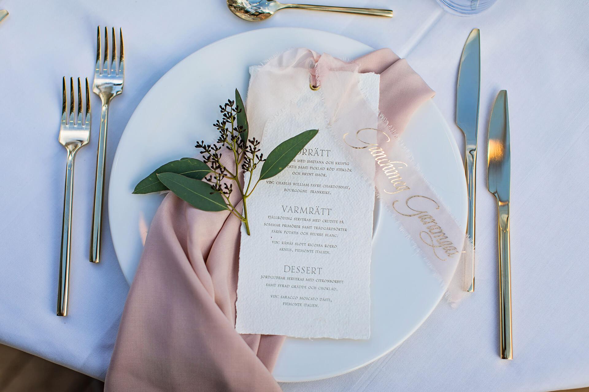 Bröllopsdukning med bestick och meny samt blommarrangemang
