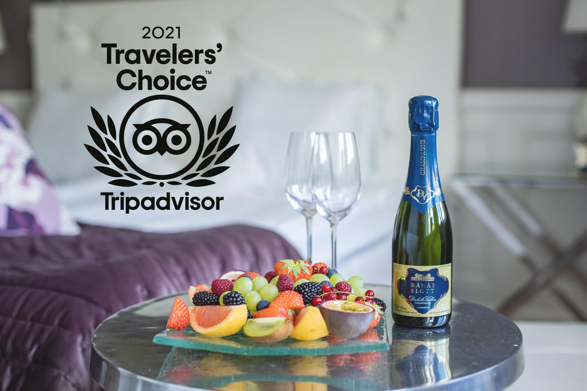 En flaska champagne och frukt samt logga Travelers choice